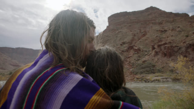 slo mo. young man holds woman and kisses her forehead as they stand by river on moab camping trip. - forehead stock videos & royalty-free footage