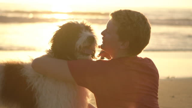 CU Young man hugging his dog on the beach