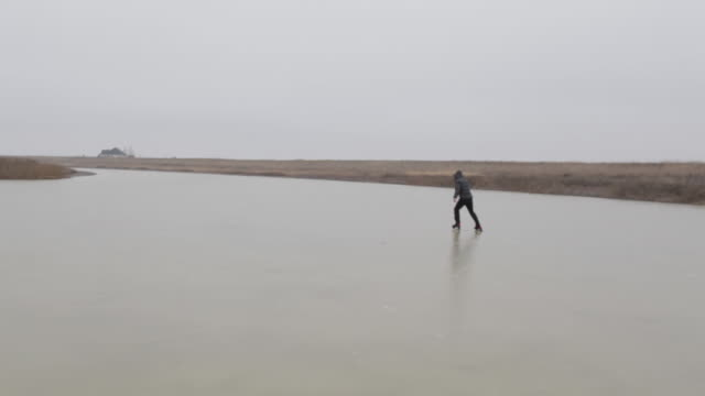 young man ice skating on frozen pond in winter in rural montana, usa. - cappotto invernale video stock e b–roll