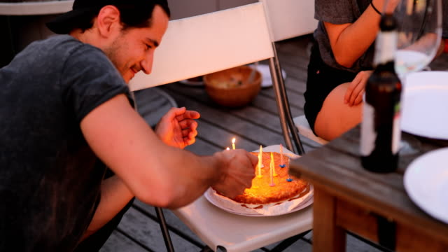 Young man igniting candles on cake with lighter