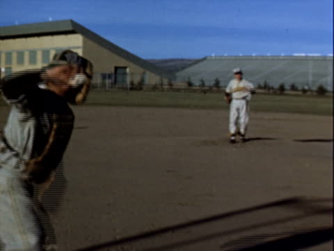 vídeos de stock e filmes b-roll de young man in a baseball jersey reading 'cowboys' up at bat catcher stands behind him the young man swings / pitcher and catcher throwing back and... - camisola de basebol
