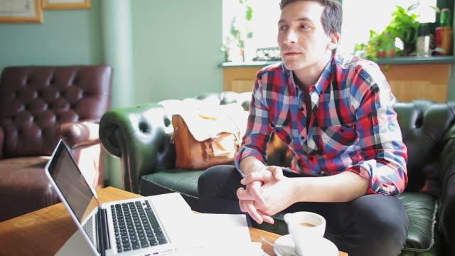 vídeos de stock, filmes e b-roll de homem jovem em um café pensar e trabalhando no laptop. - negócios finanças e indústria