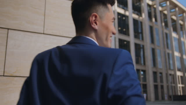 a young man in a classic business suit answers a phone call using his smartphone. a businessman receives good news. thanks to the work done, the startup has achieved success! now nothing will limit him, just go ahead! - full suit stock videos & royalty-free footage