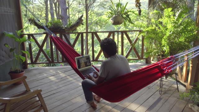 vídeos de stock e filmes b-roll de young man in a hammock using a computer. digital nomad working in a remote work. cabin retreat - brief - cabana de madeira