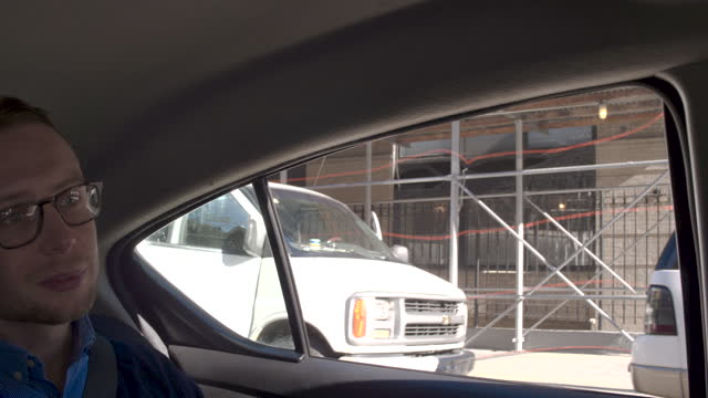 Young man in back seat at car, beautiful sunny day NYC