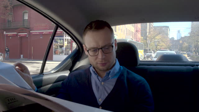 young man in back seat at car reading newspaper, daytime - newspaper stock videos & royalty-free footage