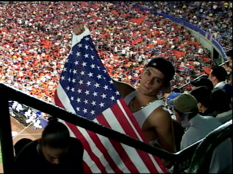 WS young man in backwards baseball cap holding American flag says We will not give up our freedom to CAM Shea Stadium First MLB baseball game after...