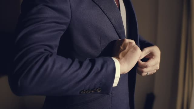 young man in black suit approaches a window. groom preparing for a wedding day. morning before ceremony - formal businesswear stock videos & royalty-free footage