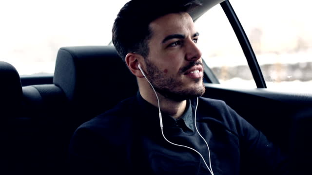 Young man in car listening music