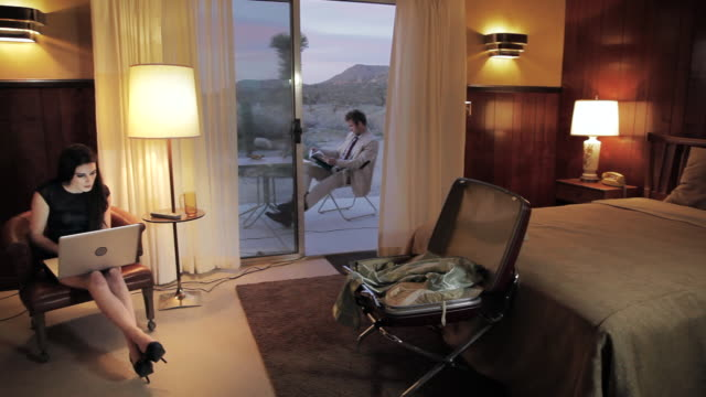 MS PAN Young man in elgant outfit sitting at outside of hotel room, redaing  magazin and woman sitting in chair, woring on laptop / Palmdale, CA, United States