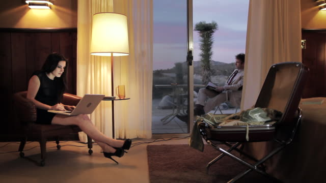 MS Young man in elgant outfit sitting at outside of hotel room, redaing  magazin and woman sitting in chair, woring on laptop / Palmdale, CA, United States