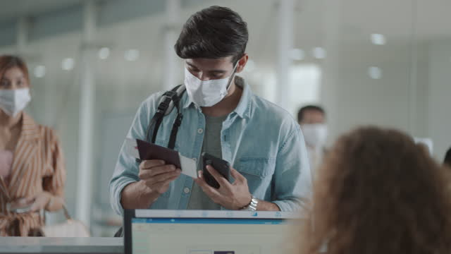young man in face mask at airport check in desk - anticipation stock videos & royalty-free footage