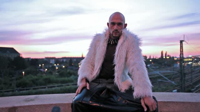Junger Mann in der fancy-outfit posieren sexy auf einer Brücke