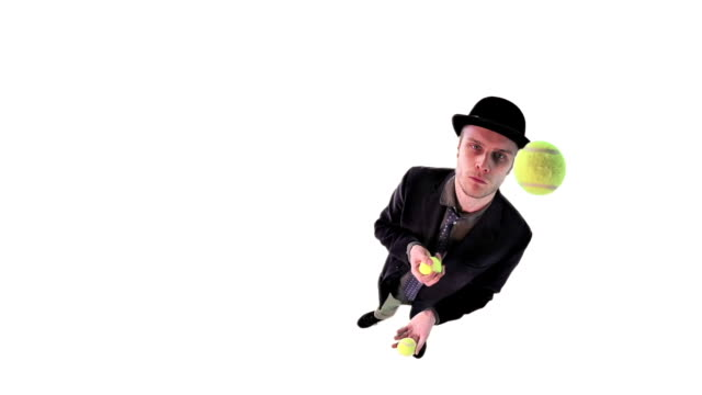 Young man in hat juggling balls