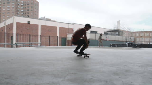 a young man in his twenties falls skateboarding at a skatepark in brooklyn, nyc - skateboardfahren stock-videos und b-roll-filmmaterial
