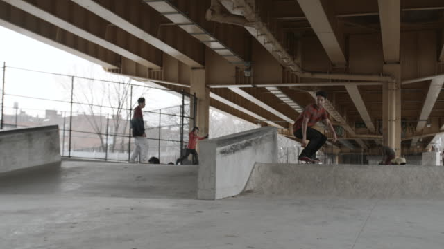 A young man in his twenties falls skateboarding at a skatepark in Brooklyn, NYC - 4k