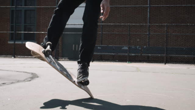 a young man in his twenties performs skateboarding tricks in the streets of brooklyn, nyc - 4k - 柵点の映像素材/bロール