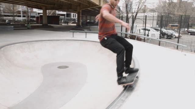 a young man in his twenties skates a ramp at a brooklyn skatepark - 4k - fence点の映像素材/bロール