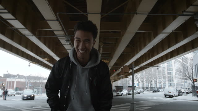 a young man in his twenties smiles for a portrait in brooklyn, new york city - 4k - fashionable stock videos & royalty-free footage