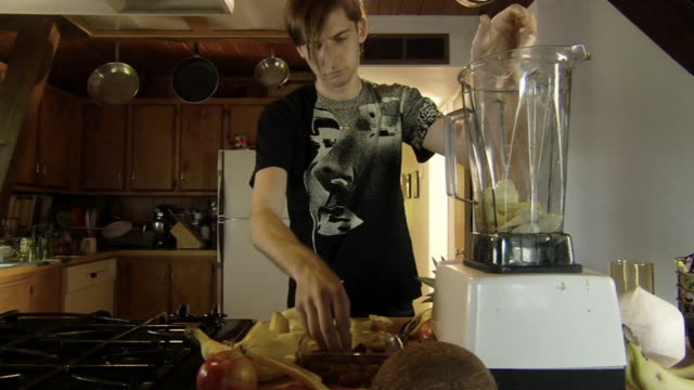 ms young man in kitchen cutting up banana and putting it in blender with grapes and soy milk to make a smoothie/ man pouring blender contents into glass and exiting/ los angeles, california - soy milk stock videos and b-roll footage