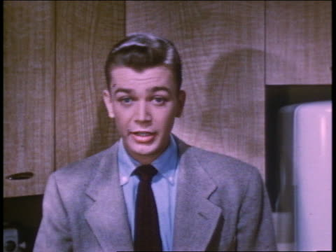 1952 young man in kitchen talking to someone offscreen - one teenage boy only stock videos and b-roll footage