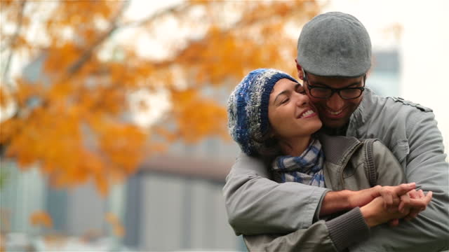 Young man in love wraps arms around and kisses girlfriend in autumn park