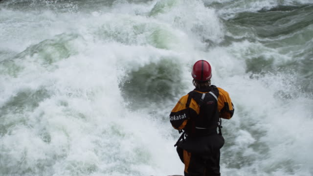 ms slo mo young man in outdoor equipment standing next to river scouting its rapids / banks, idaho, united states - nur junge männer stock-videos und b-roll-filmmaterial