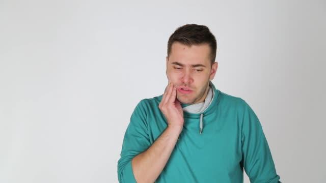 vídeos y material grabado en eventos de stock de un hombre joven con dolor de muelas, estudio, fondo blanco, actor - mano en la barbilla