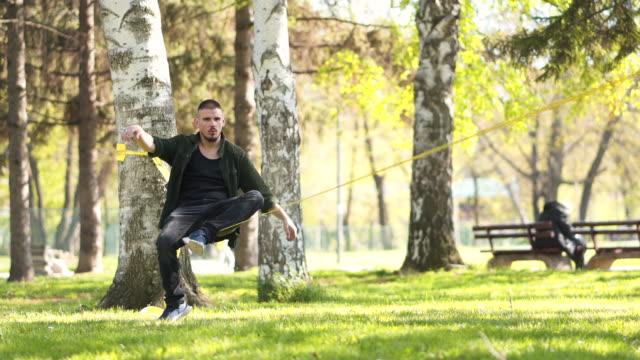 junger mann im park balanciert auf einer slackline - seil stock-videos und b-roll-filmmaterial