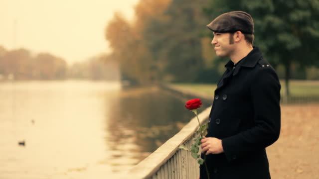 Young man in park, smelling a rose, lover
