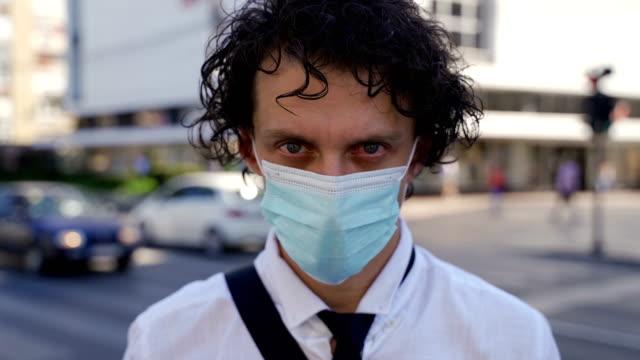 junger mann in schützender gesichtsmaske als vorbeugende maßnahme des corona-virus. - kritiker stock-videos und b-roll-filmmaterial