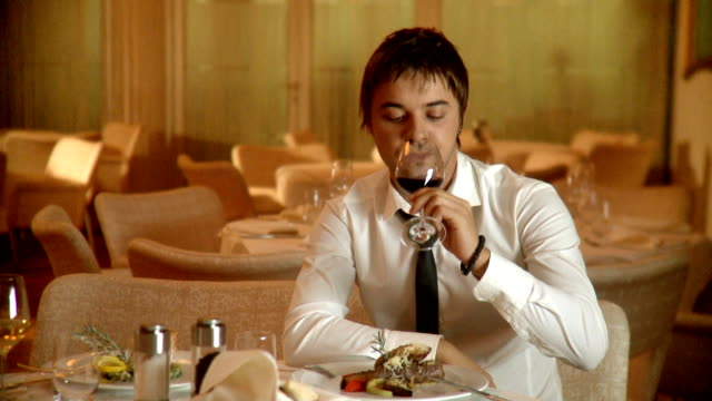 Junge Mann trinkt Wein im restaurant