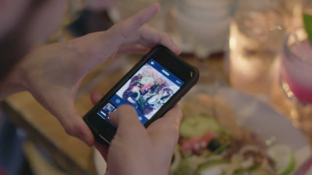 vidéos et rushes de young man in restaurant takes photo of his food and uses smartphone app to edit it - blog