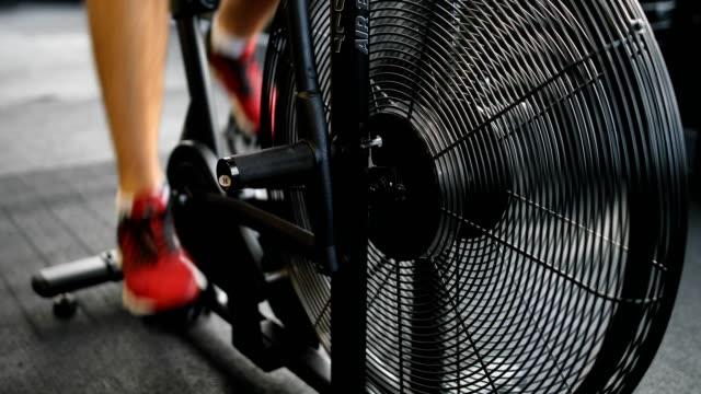 junger mann in sportschuhen radfahren im fitness-studio - heimtrainer stock-videos und b-roll-filmmaterial