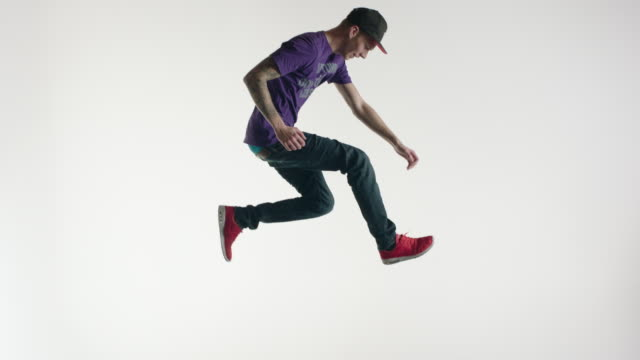 young man in streetwear doing acrobatics in the air - white background stock videos & royalty-free footage