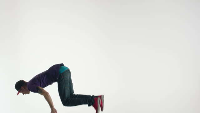 Young man in streetwear doing acrobatics in the air
