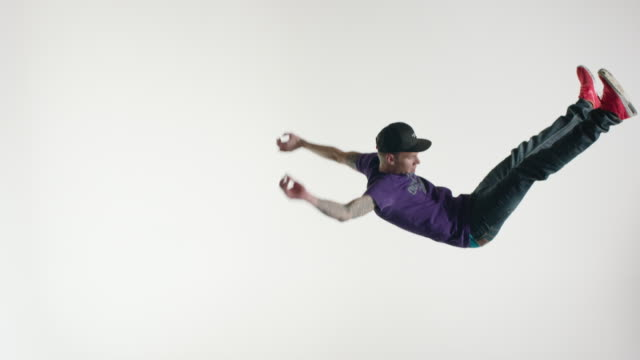 vídeos y material grabado en eventos de stock de young man in streetwear doing acrobatics in the air - flotando en el aire
