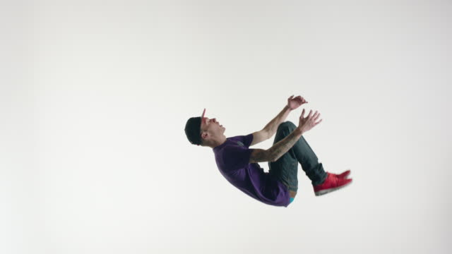 stockvideo's en b-roll-footage met young man in streetwear doing acrobatics in the air - acrobatiek