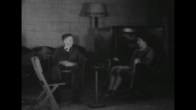 stockvideo's en b-roll-footage met young man in suit and tie talking to a woman both sitting on rocking chairs lamp in the background - schommelen schommelstoel
