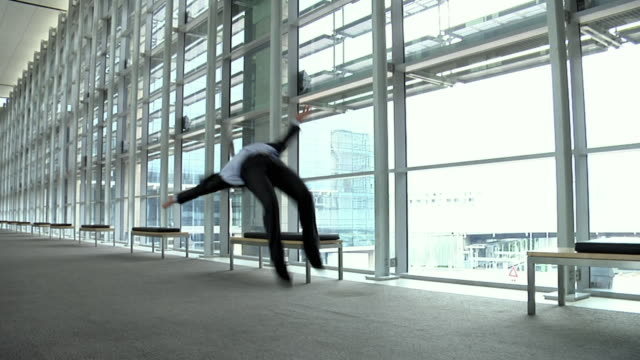 SLO MO WS Young man in suit doing forward flips in office building hallway, Cape Town, South Africa