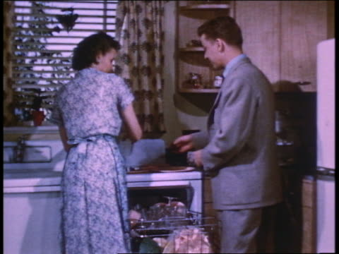1952 young man in suit talking to mother loading dishwasher in kitchen - lavastoviglie video stock e b–roll