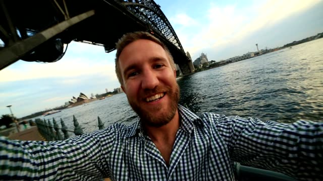 Young man in Sydney harbour, takes a selfie portrait