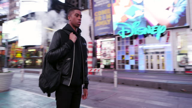 young man in times square in new york city in revolving motion shot - 立つ点の映像素材/bロール