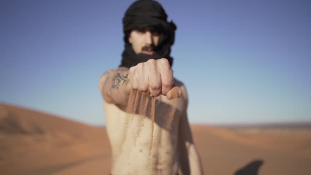 young man in turban dropping sand from the sahara desert - shirtless stock videos & royalty-free footage