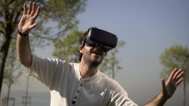 Young Man In Virtual Reality Headset or VR Glasses Outdoors