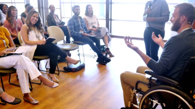 young man in wheelchair addresses crowd of businesspeople - pamphlet stock videos & royalty-free footage