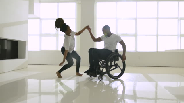 young man in wheelchair dancing with female partner - disability stock videos & royalty-free footage