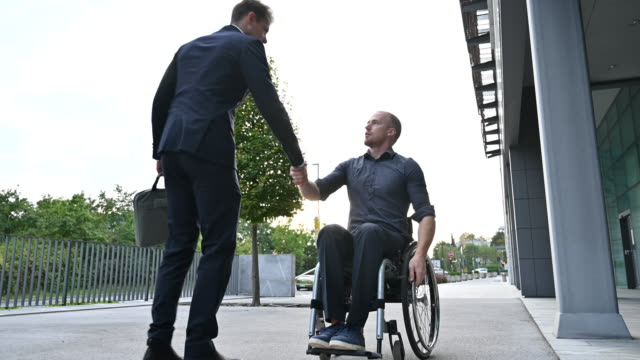 young man in wheelchair meeting mid adult businessman - persons with disabilities stock videos & royalty-free footage