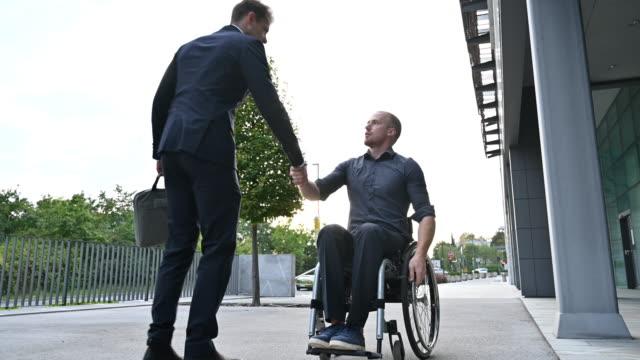 vídeos y material grabado en eventos de stock de joven en silla de ruedas que se reúne con un hombre de negocios de fin de adulto - personas con discapacidad