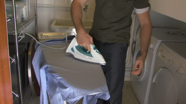stockvideo's en b-roll-footage met ms zo tu young man ironing shirt / hackney, united kingdom      - strijkijzer